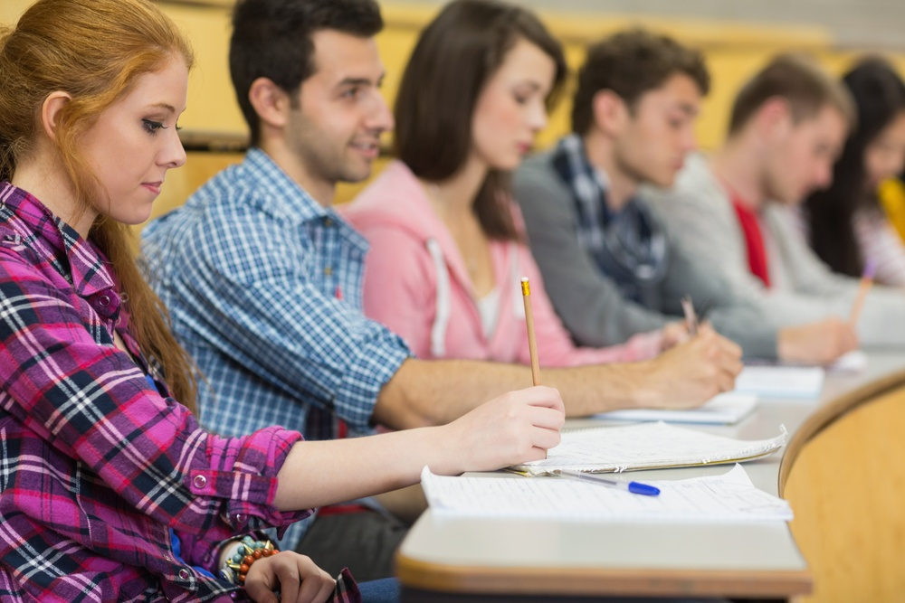 Side view of students writing notes in a row at the college lecture hall.jpeg
